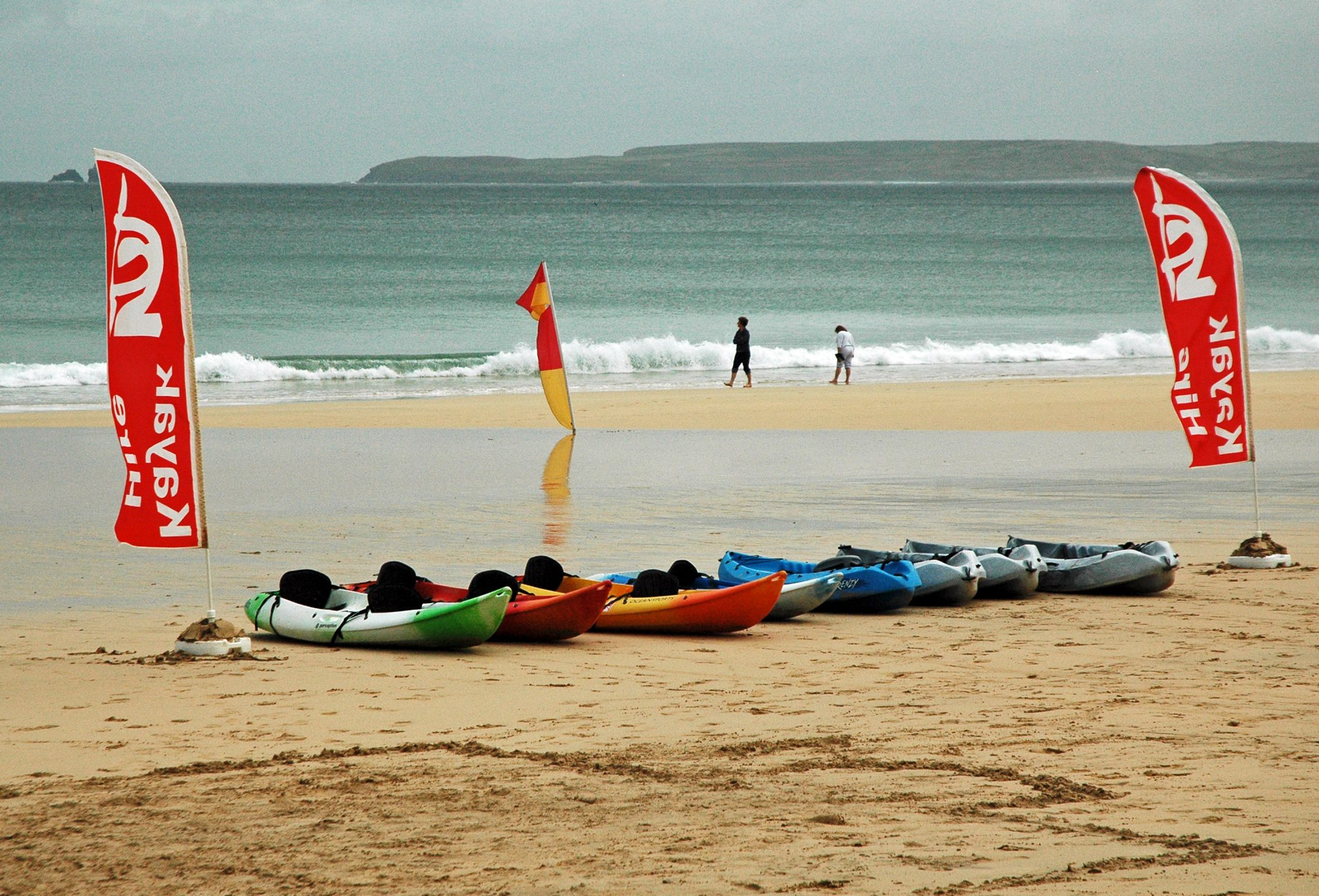 A colourful line up of kayaks offered for hire on Carbis Bay beach by Ocean Sports. www.carbisbayholidays.co.uk