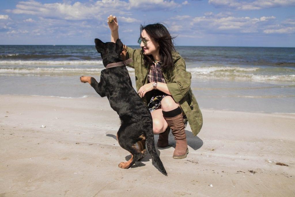 Girl with black dog on Cornish beach