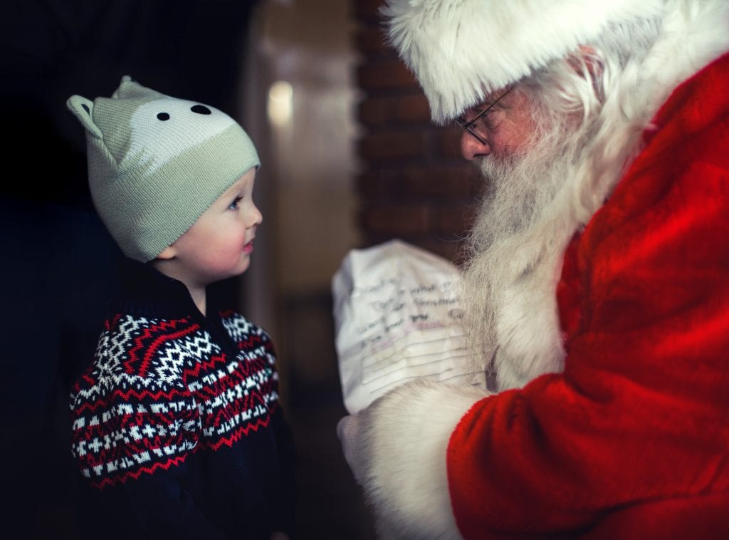 Santa Claus giving young boy a Christmas gift