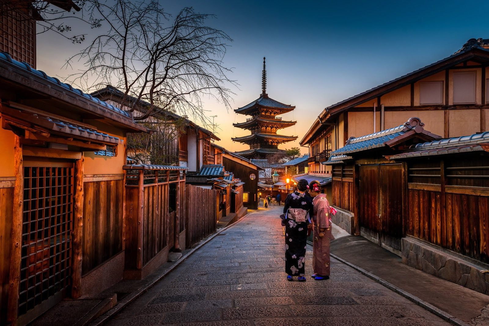 street in Japan with old style building and two geishas walking