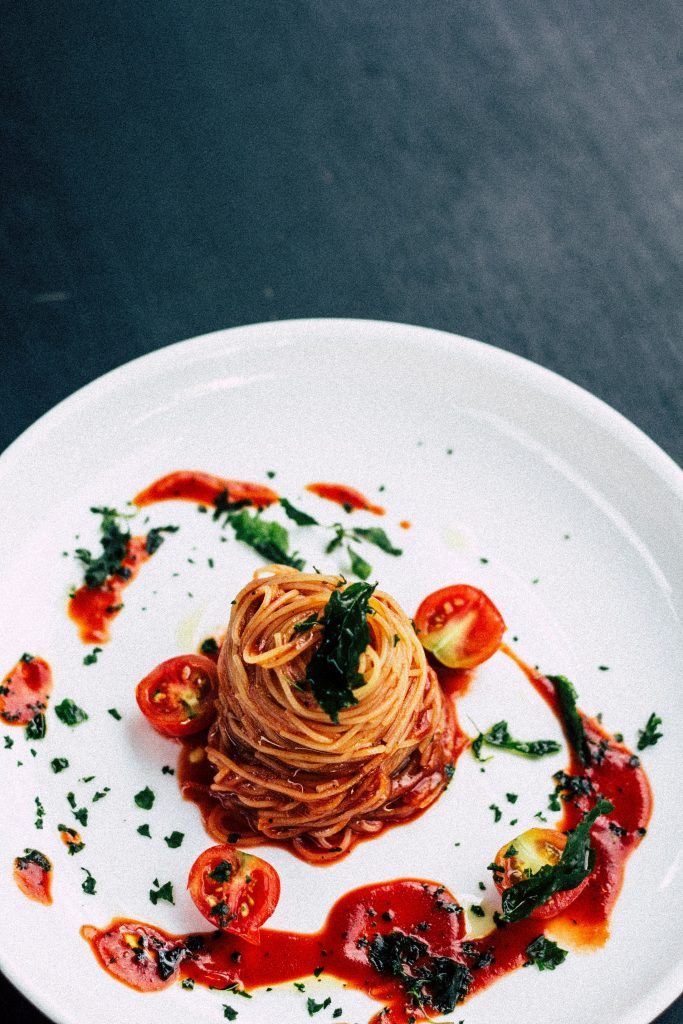 White Plate of Spaghetti ao Sugo decorated with cherry tomatoes from one of the Italian Restaurants in St Ives