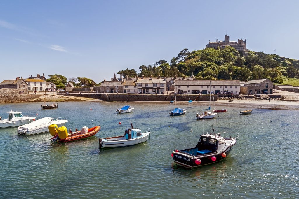 View towards St Michaels Mount Cornwall. Boats can be seen in the harbour and people can be seen on the promenade.