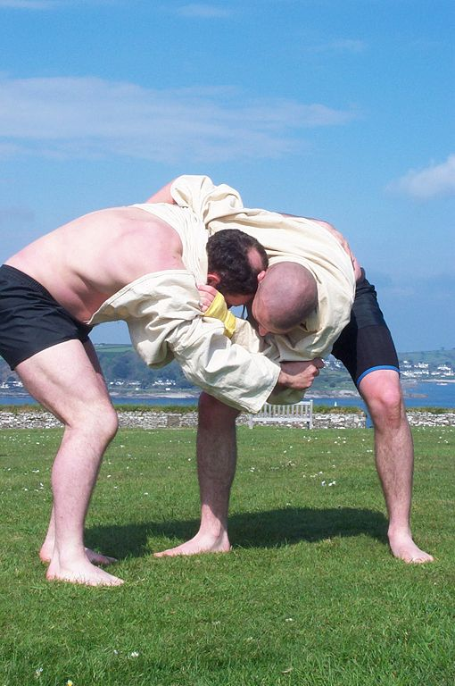 Two men wrasslin on a field