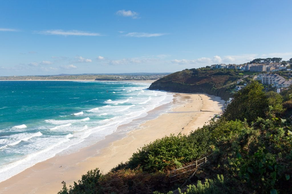 A view of Carbis Bay beach from the south west coastal path on a sunny day.