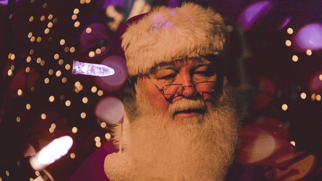 Santa in Cornwall under Christmas lights with glasses