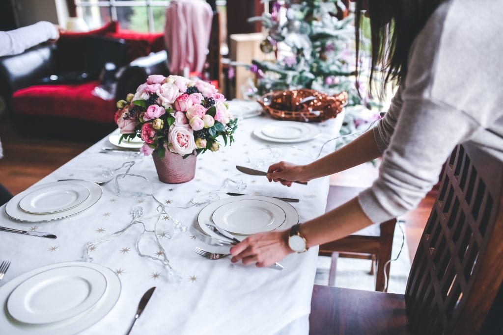 Woman laying cutlery for restaurant Christmas dinner