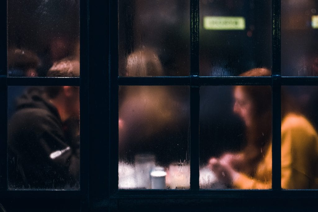 Woman and man in restaurant behind condensation in glass