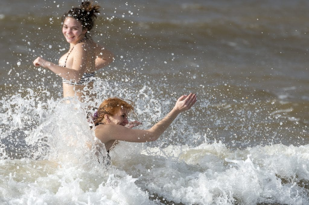 Two girls playing in Cornish waves on Christmas