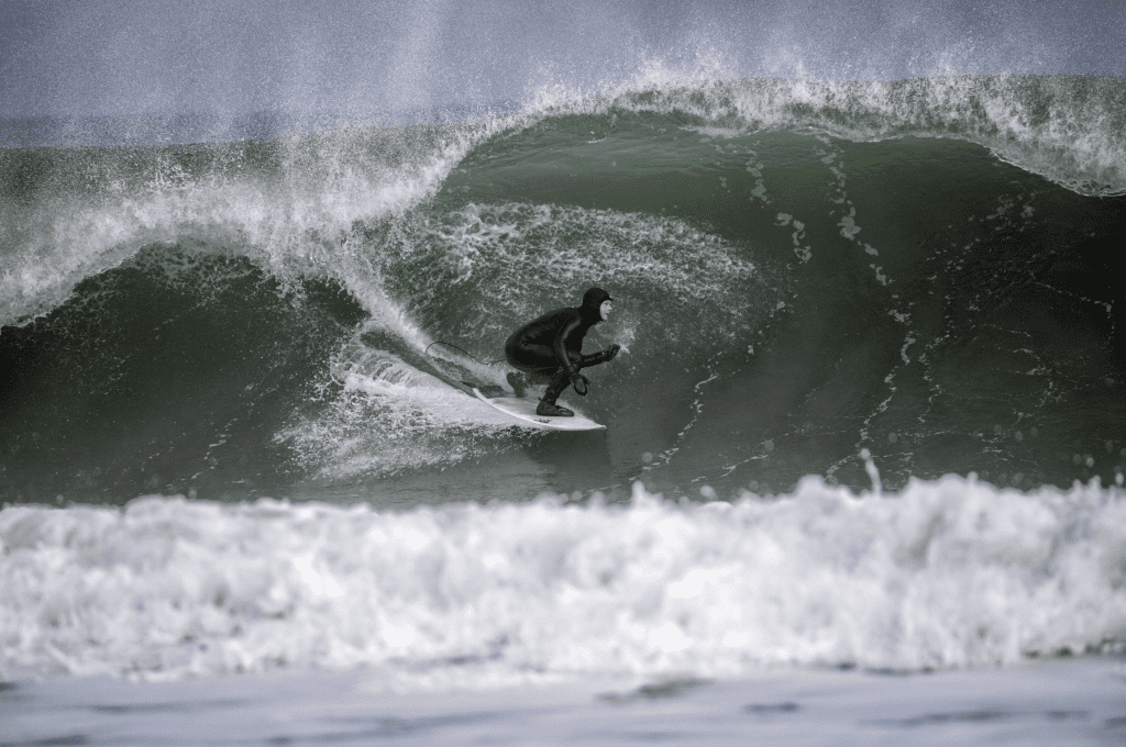 Cold water surfer wearing a hood surfing a wave
