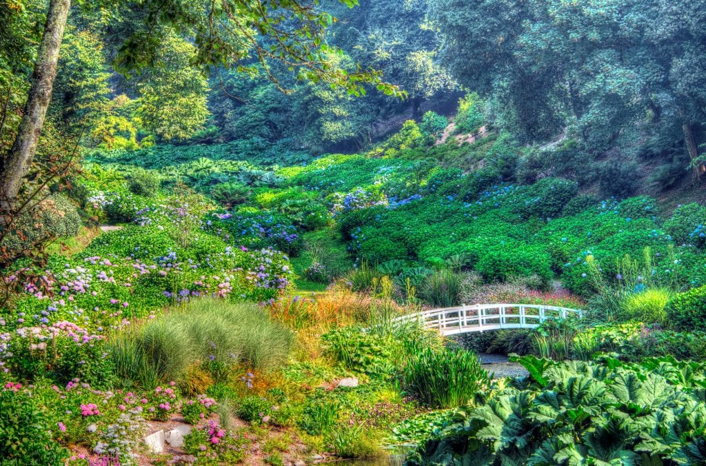 Gardens in a valley with flowers and shrubbery with a white draw bridge over a stream.