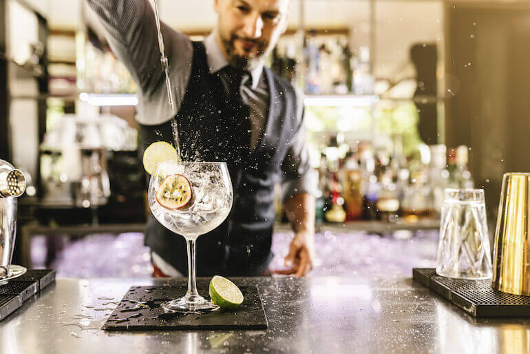 bartende pouring gin in a bowl glass