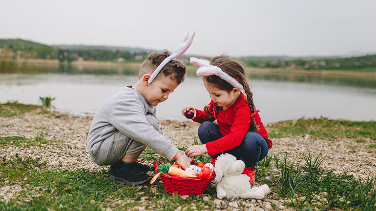 Brother and sister hunting for eggs on Easter