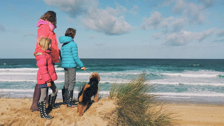family with dog on beach in cornwall