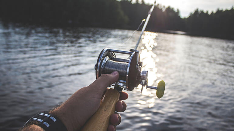 male hand holding a fishing rod