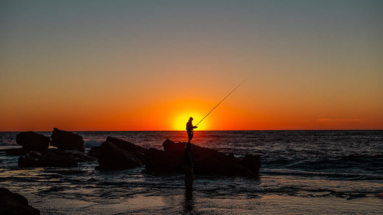 fishing in Cornwall against a bright sunset