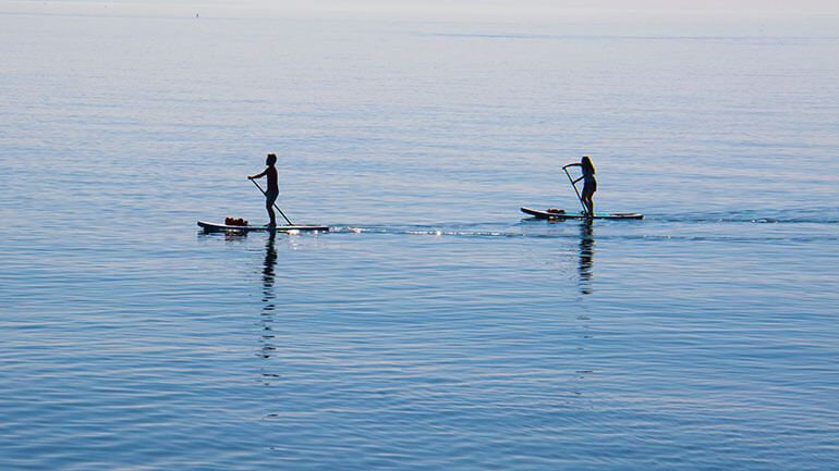couple paddleboarding in Cornwall